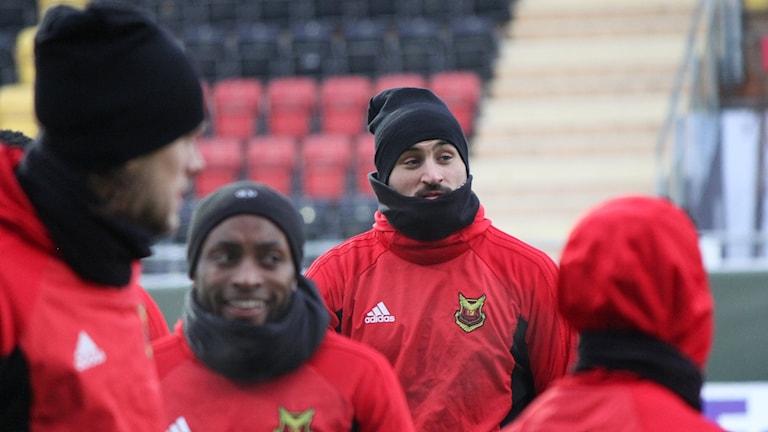 Fyra fotbollsspelare klädda för träning i kyla på fotbollsarena