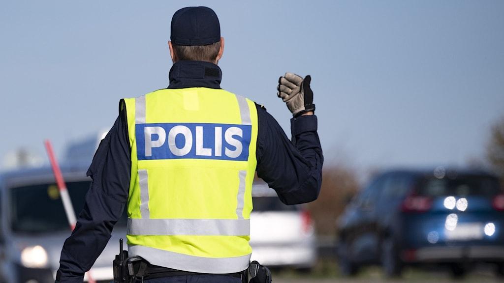Polisman med gul reflexväst vinkar in bilist på väg