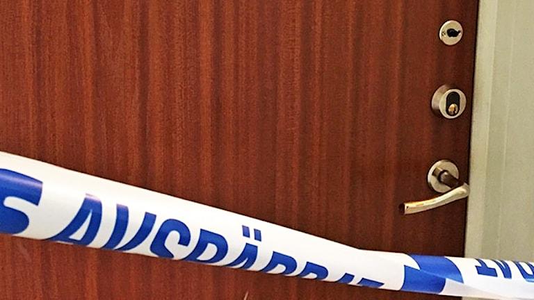 Plastband polisavspärrning framför lägenhetsdörr