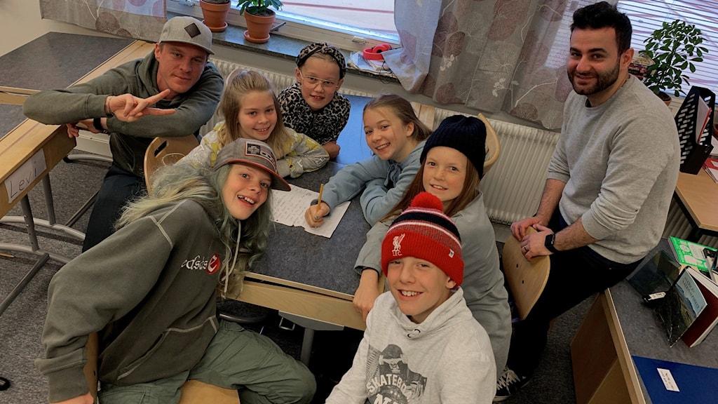 Sex skolelever sitter runt en skolbänk och bakom står två vuxna killar.