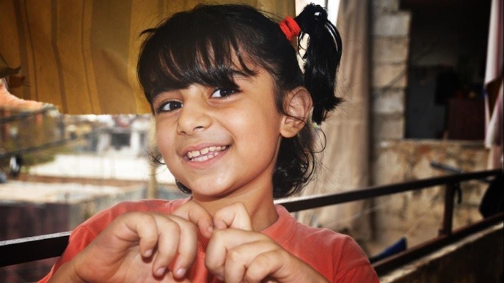 Mörkhårig flicka med råttsvansar ler mot kameran och formar hjärta med fingrarna
