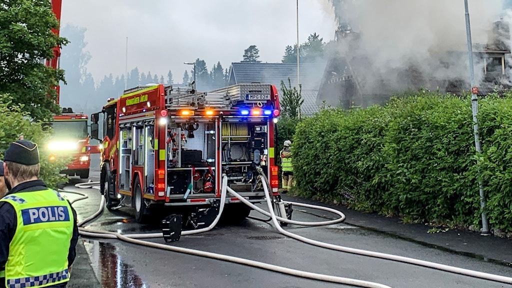 Brandbil med utrullade slangar står fram ett brinnande hus på en gata i ett villaområde.