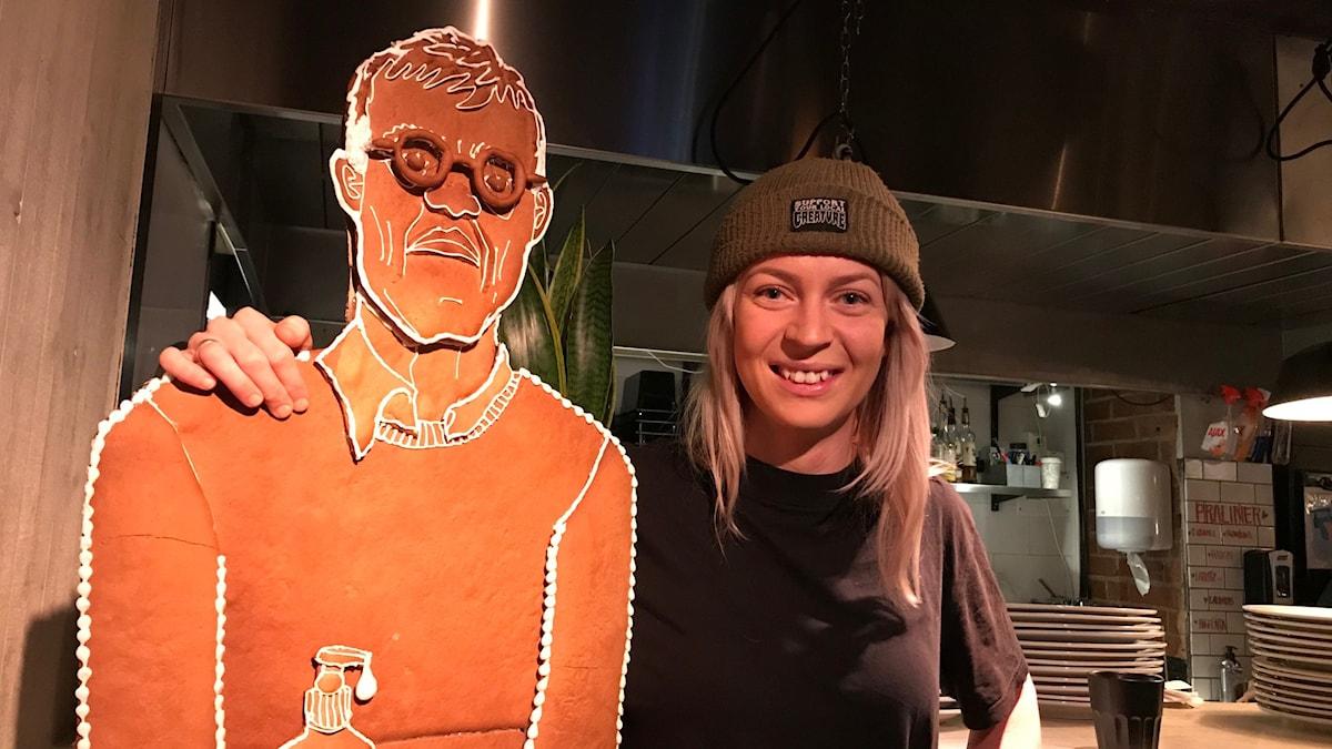 Kvinna som står tillsammans med en pepparkaka som ser ut som Anders Tegnell.