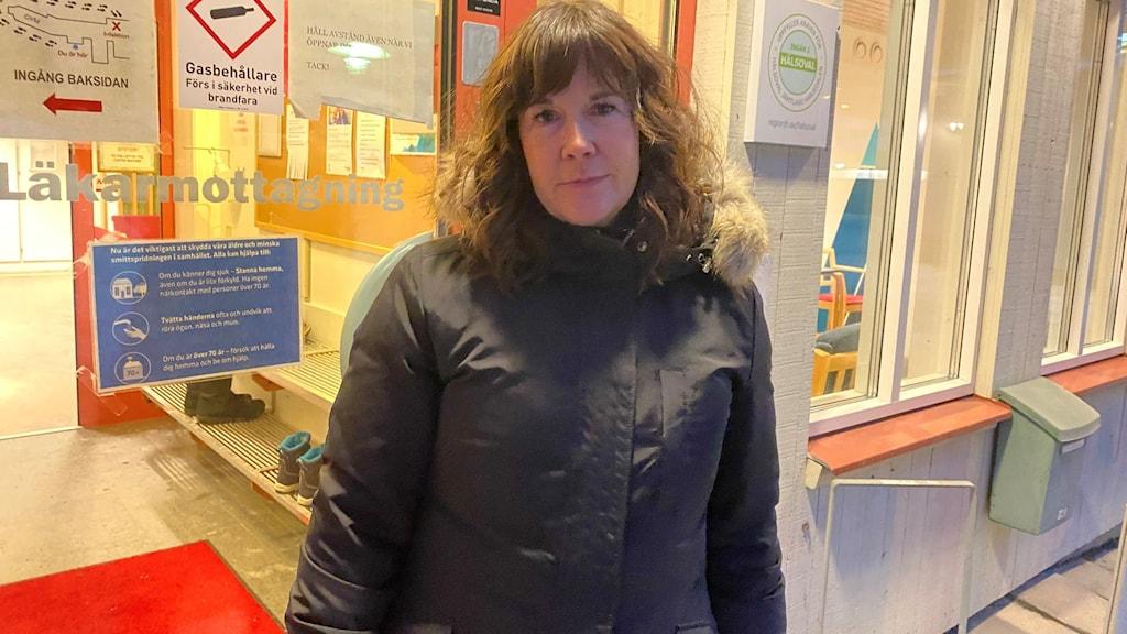 En kvinna i svart jacka och långt krulligt hår utanför en hälsocentral i Åre