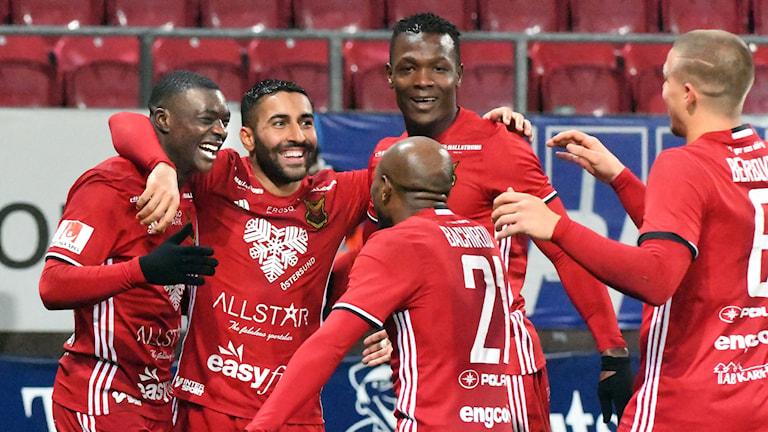 Fem fotbollsspelare kramar om varandra