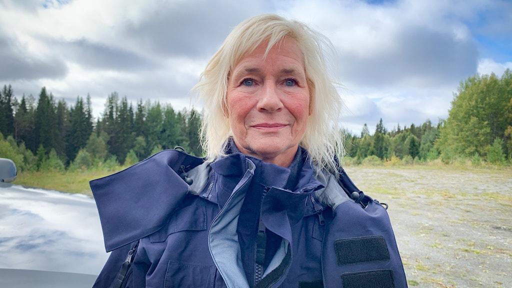Ljushårig kvinna med tjock, mörkblå jacka i skogsmiljö.