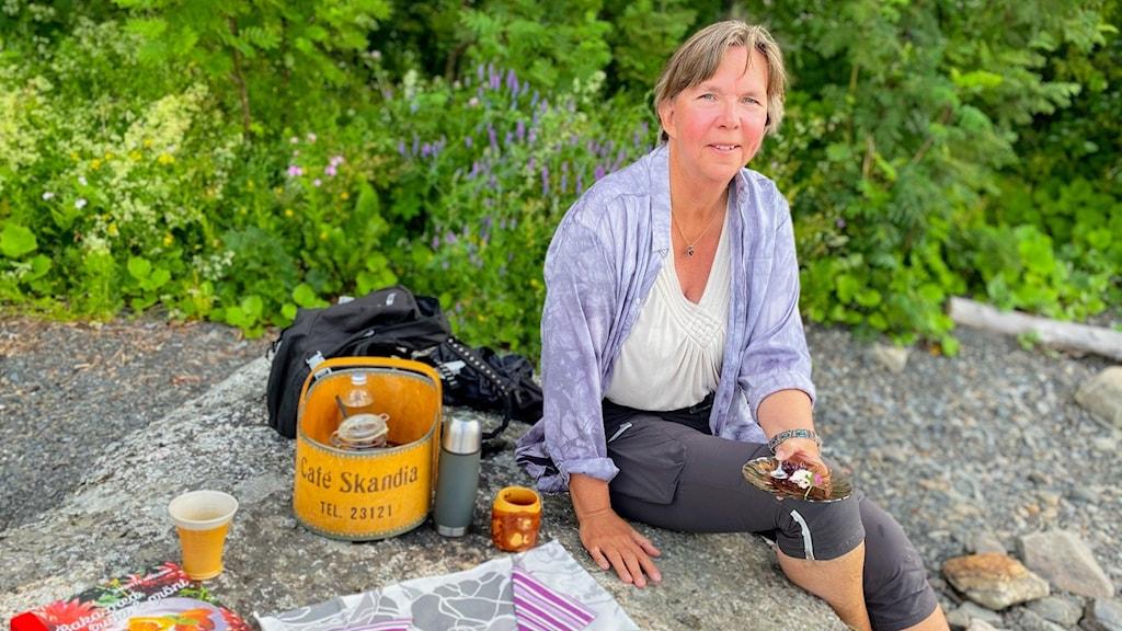 En kvinna som sitter på stenhäll med fika.
