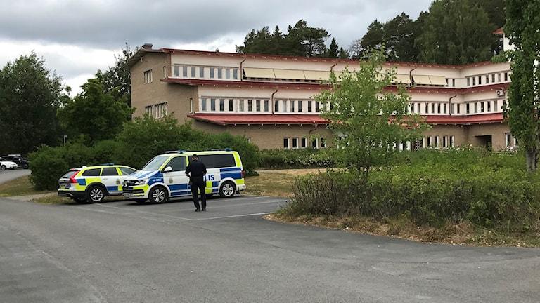 Polisbilar står utanför byggnad