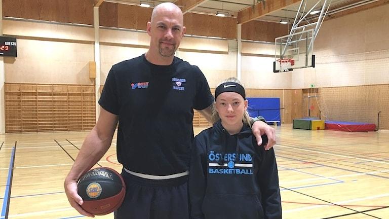 Baskettränaren RT Guinn håller i en basketboll. Bredvid honom står en ungdom som tränar basket.