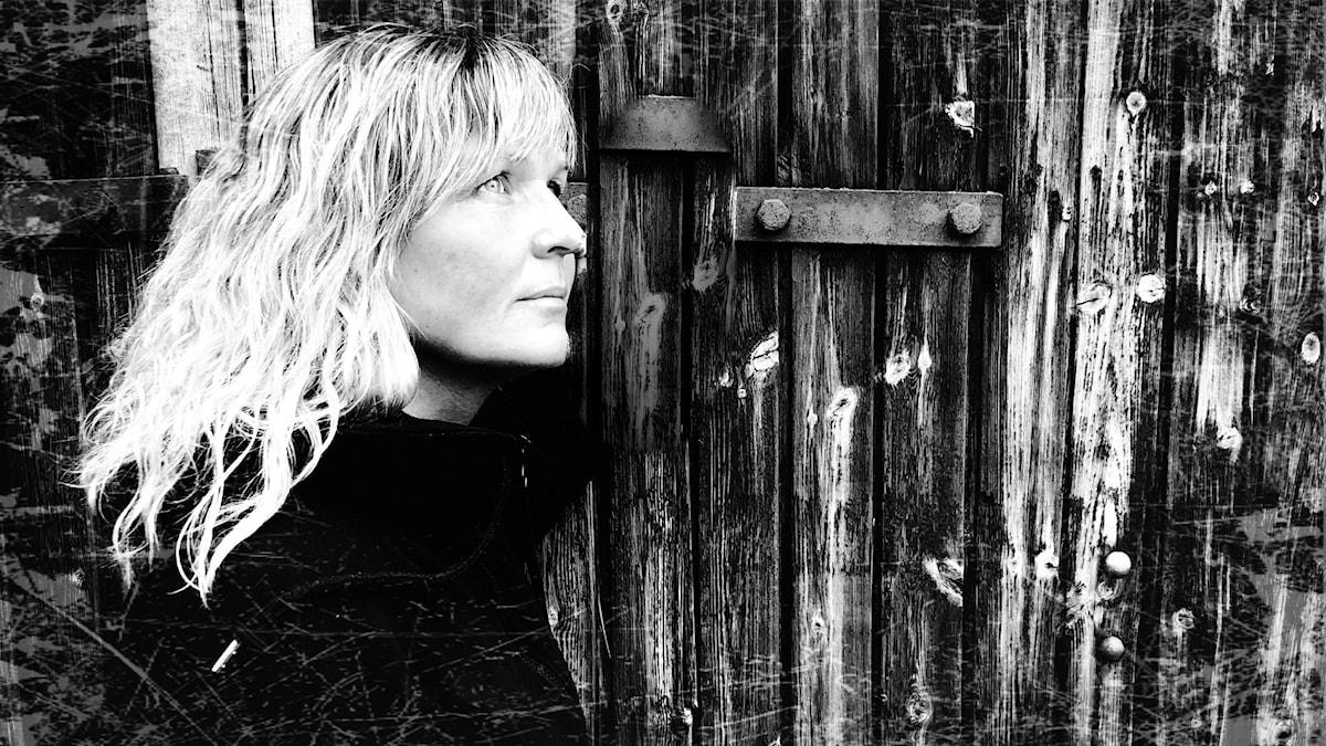 Kvinna som står mot en mörk väg utomhus, det är en svartvit bild.