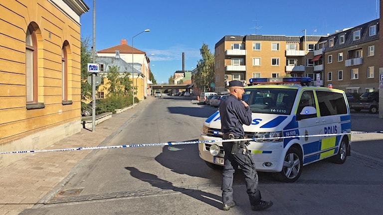Polisman och polisbild vid polisavspärrning på stadsgata