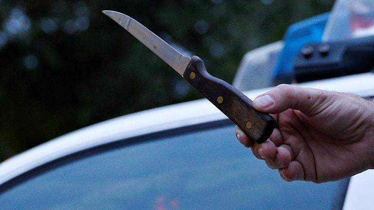 Hand håller kniv bredvid polisbil