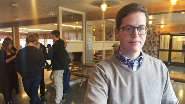 Ung man med glasögon i skollokal med ungdomar