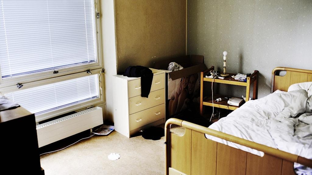 Ett tomt rum med en obäddad säng och neddragna persienner