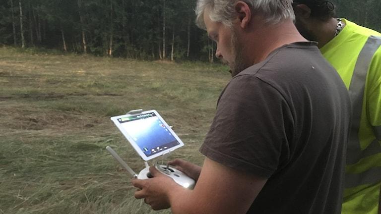 En man i grå tshirt som håller en skärm och en fjärrkontroll framför sig