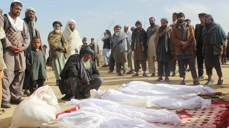 Krigsdödade människor ligger övertäckta på marken men sörjande människor runtomkring