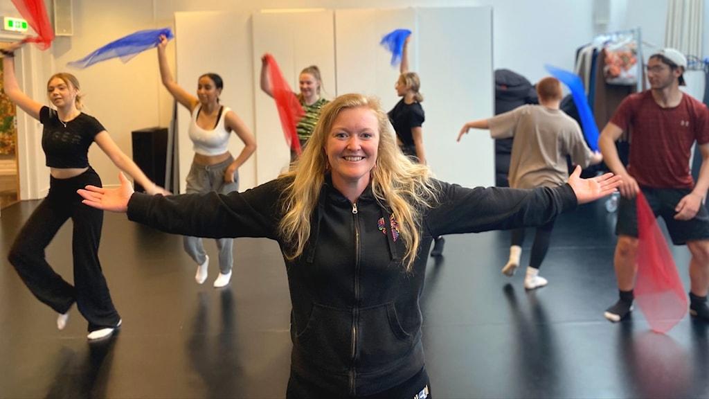 En kvinna i ljust lockigt hår står framför en grupp med ungdomar som dansar