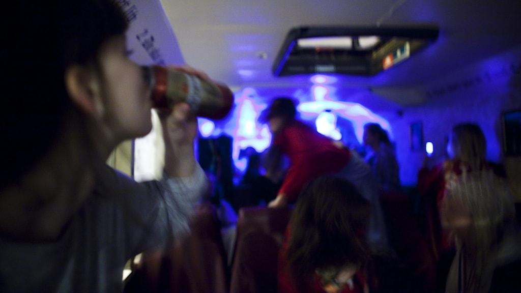 Tjej till vänster i bild dricker ur flaska, i nattklubbsmiljö.