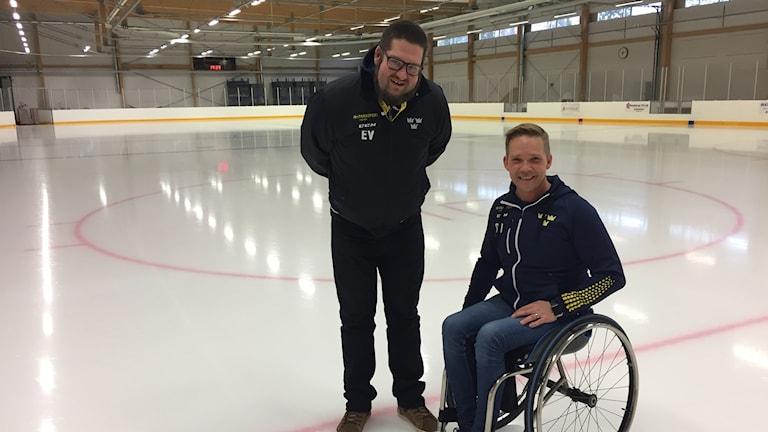 Två män poserar ute på en ishockeyrink.