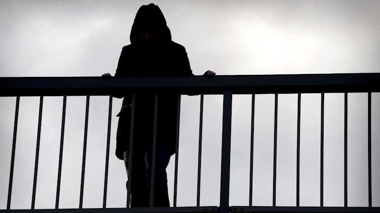 En deprimerad kvinna står på en bro och funderar på att ta livet av sig.