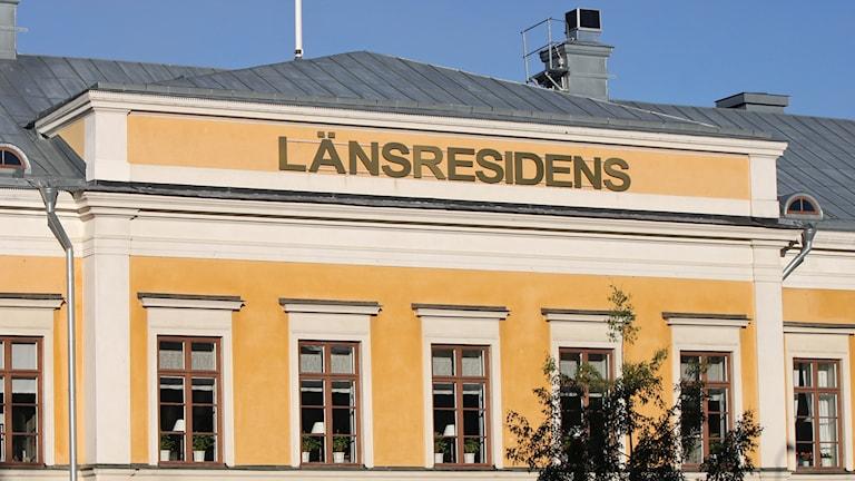 Byggnad med gul fasad, plåttak och fönster med spröjs