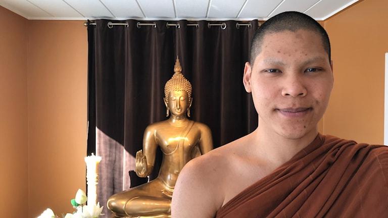 Buddhistmunk står framför buddha-staty i tempel