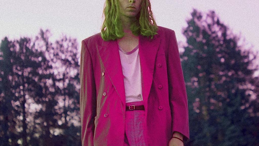 Man i rosa kostym och långt ljust hår.
