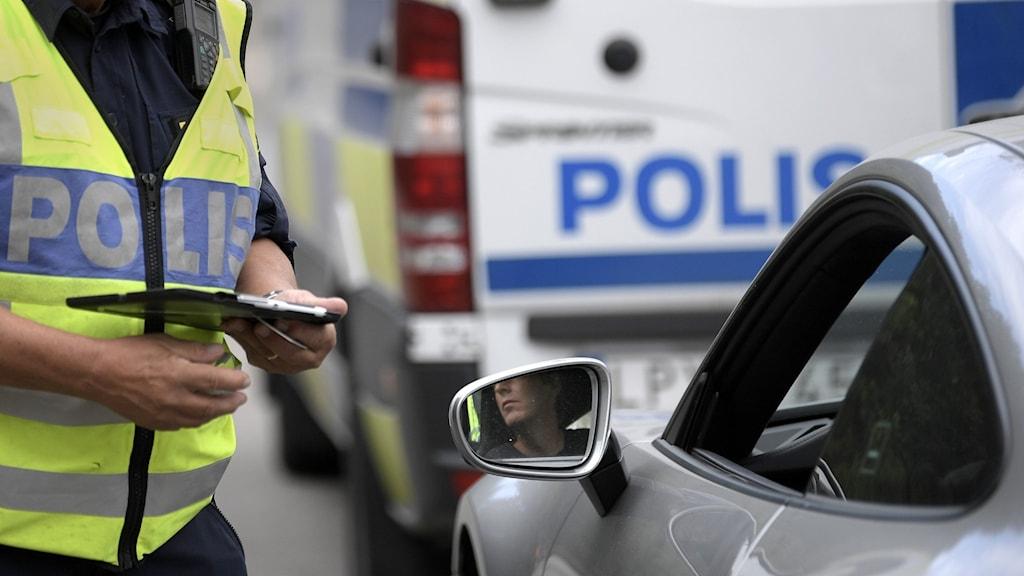 Polisman skriver ut böter till bilist i personbil