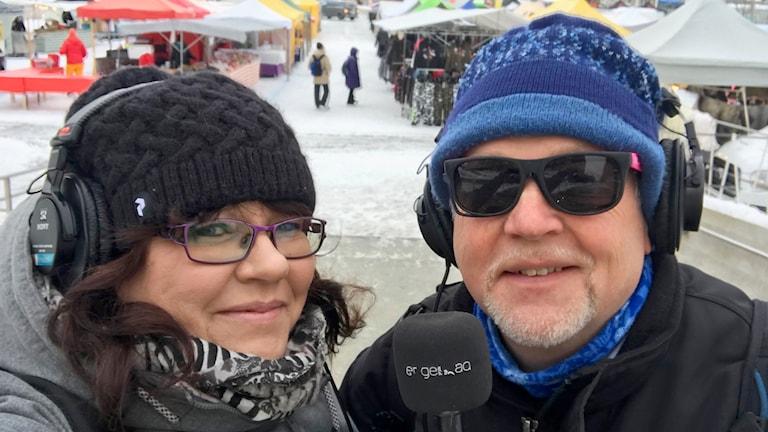 Man och kvinna med hörlurar och solglasögon på marknad