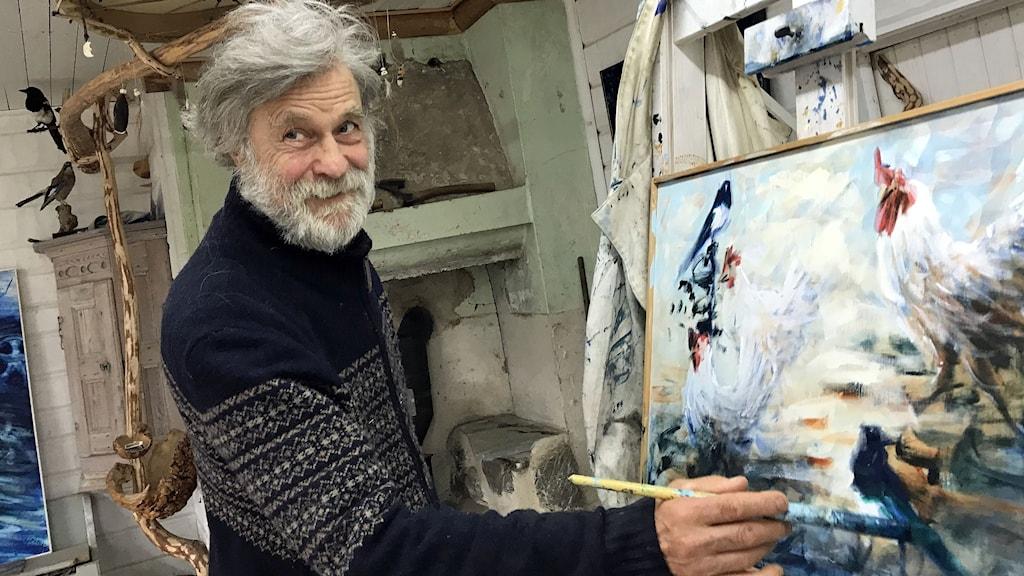 man med grått rufsigt hår står vid staffli och målar höns på en målarduk med akrylfärg