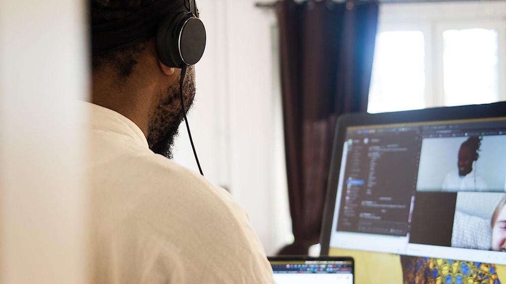 En man som syns bakifrån som sitter framför en dator.