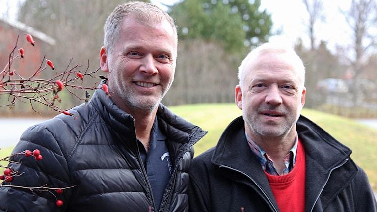 Två män i ytterjackor står vid en nyponbuske