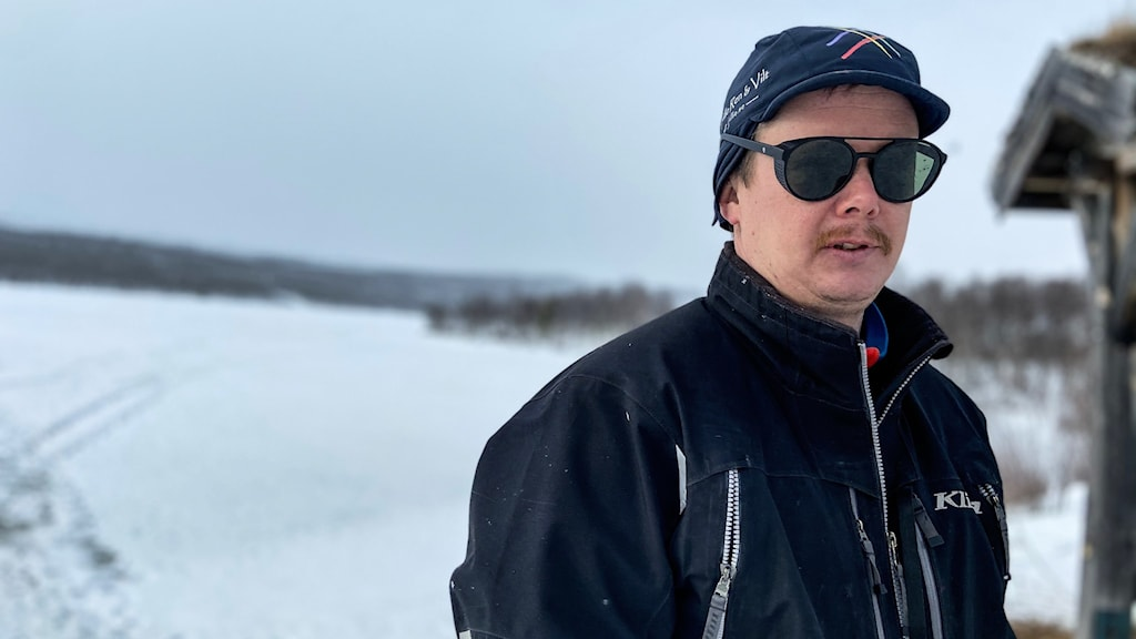En man med mörkblå jacka, keps och solglasögon står vid en frusen sjö.