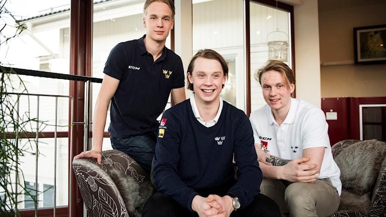 Tre killar sitter i en soffa