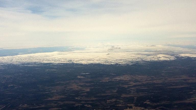 Vy över fjäll från flygplansfönster