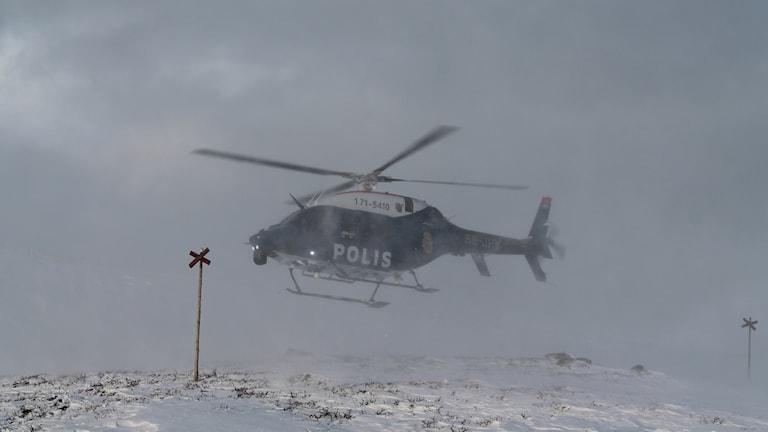 Polishelikopter landar på snöigt fjäll