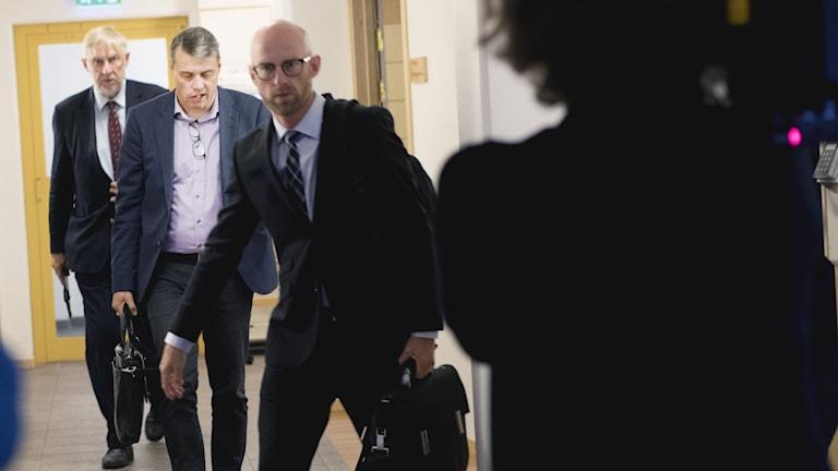Tre män i kostym filmas i korridor