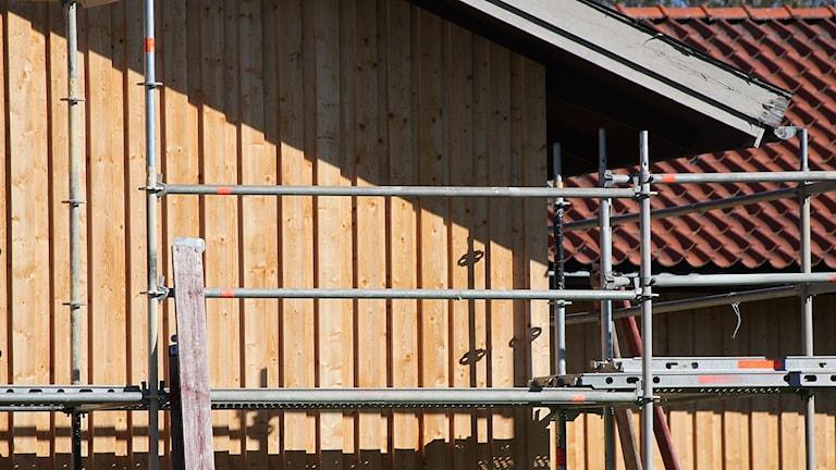 Byggställning står mot omålad trähusfasad