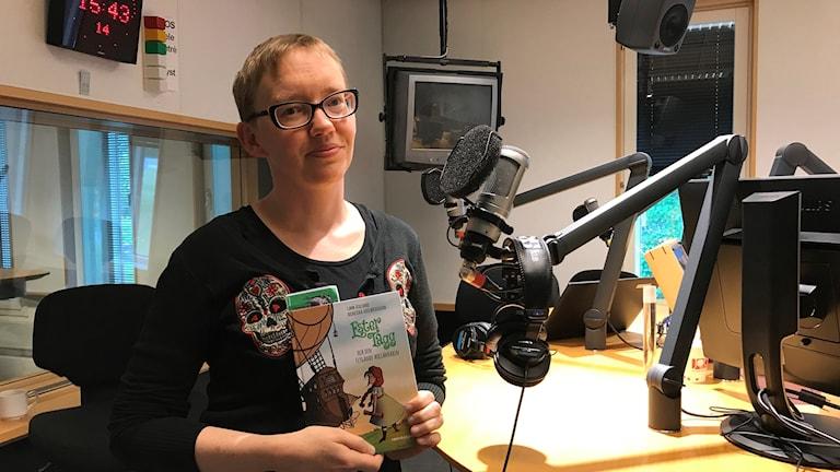 Kvinna står i radiostudio med bok i handen.