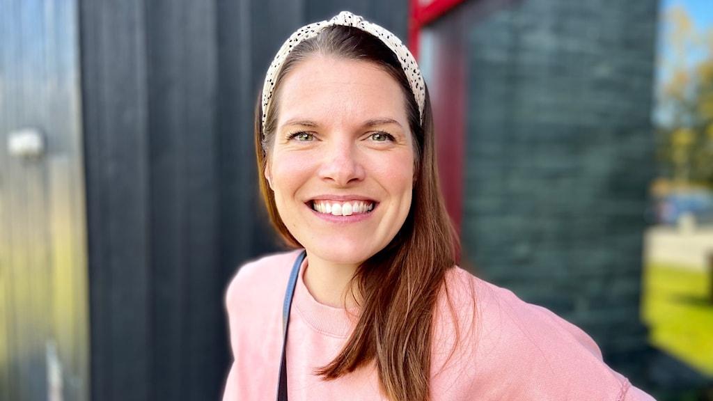 Kvinna med rosa tröja står mot husvägg och ler