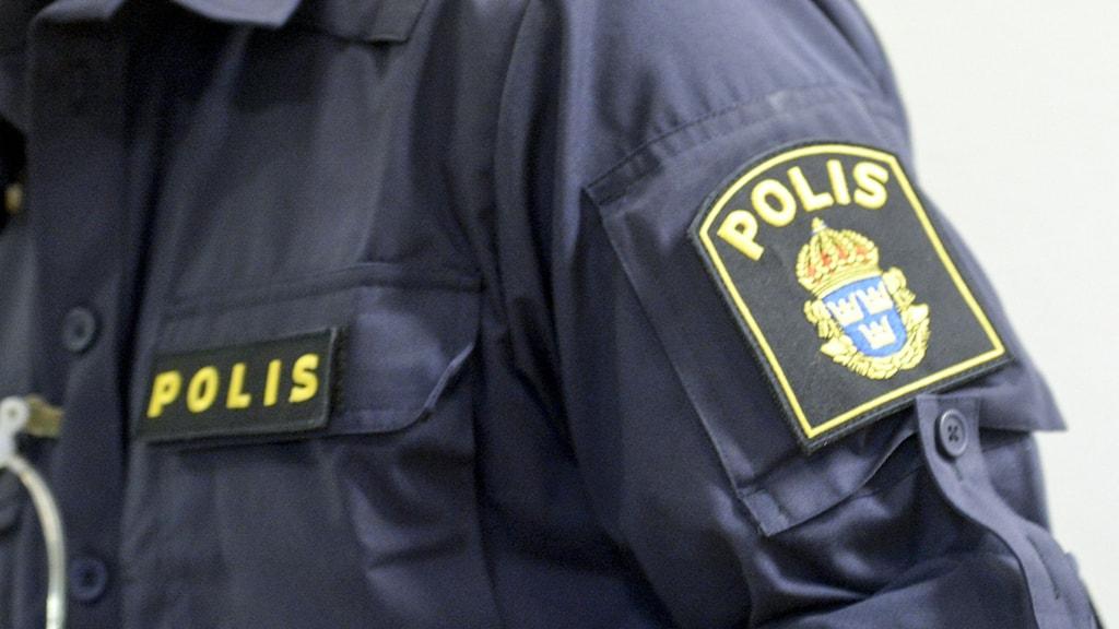 Man i polisskjorta, ansiktet syns inte