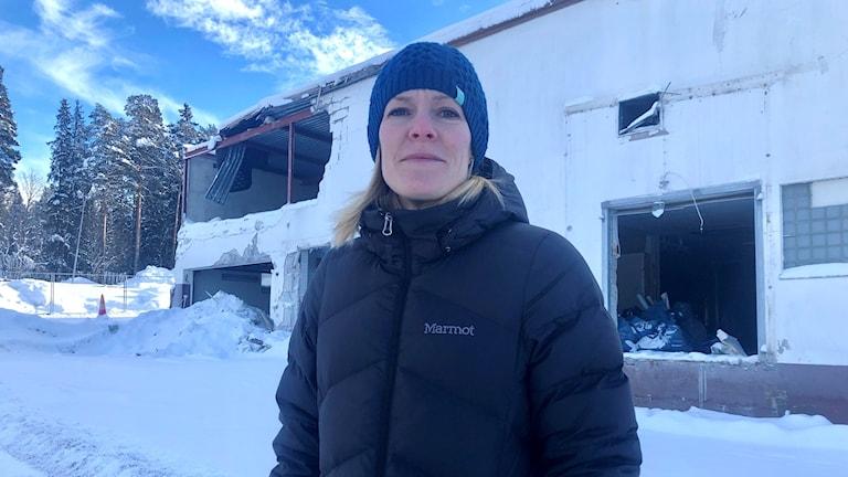 Kvinna i vinterkläder framför fallfärdig byggnad