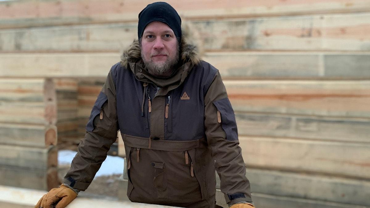 En man med blont skägg i vinterjacka vid ett timmerhus