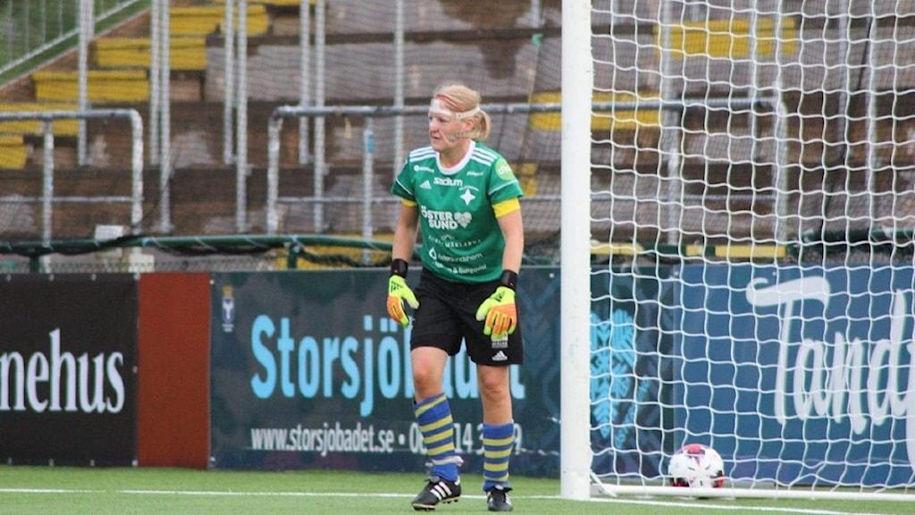 En kvinna i svarta shorts, grön t-shirt, handskar och fotbollsskor står framför ett fotbollsmål.