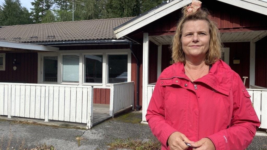 Kvinna i röd kappa utanför ett hus.