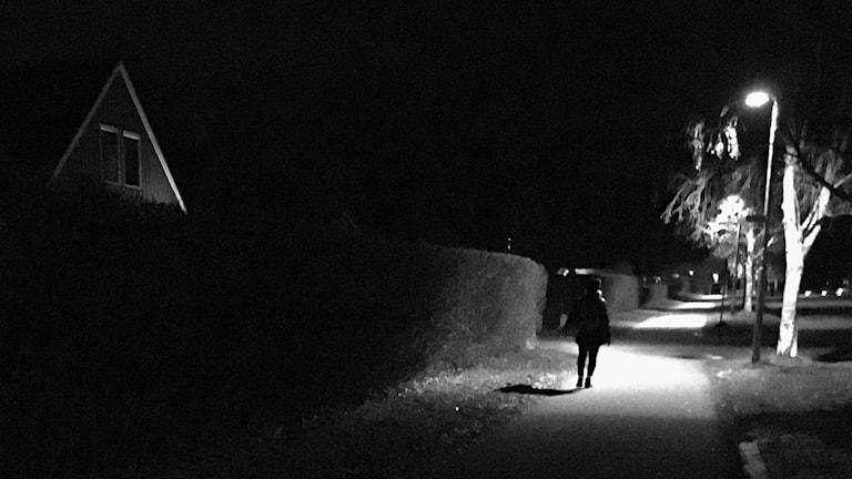 Kvinna går i mörker på gångväg i bostadsområde