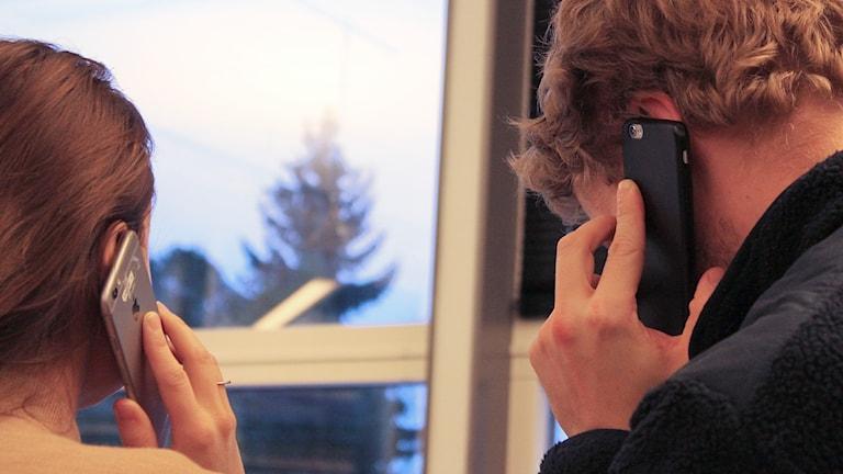Man och kvinna pratar i varsin mobiltelefon