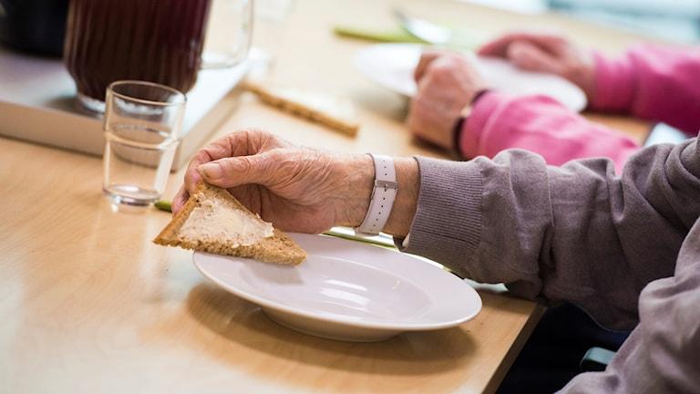 En gammal hand håller en smörgås vid matbord