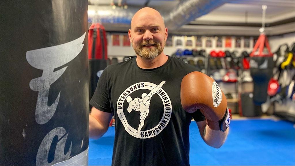 Man med kal hjässa och skägg i svart t-shirt med klubbemblem boxar mot en slagpåse i ett gym