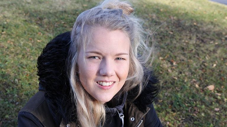 Ung kvinna med blont hår sitter vid gräsmatta